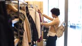 consumidor : Young american woman in boutique selecting new clothes to buy. Happy smiling african girl with curly hair looking at red dress in a fashion store. African woman doing shopping in a new clothing store and checking the dresses. Stock Footage