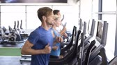 бегать трусцой : Fitness girl and guys running on treadmill at gym. Young fit people running on treadmill. Fitness and healthy lifestyle concept.