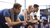 ginásio : Fitness happy woman on stationary bicycle doing spinning at gym. Fit young woman working out on bike with man. Smiling girl exercising with group of people and looking at camera. Stock Footage
