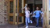 Smiling elementary school children happy to go home. Joyful school girls and boys wearing backpack and running outside the school at the end of the lessons. Teacher holding door while students running out.