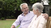 women : Senior couple sitting together on bench at park. Elderly married couple sitting outdoor and relaxing. Romantic husband embrace his wife while looking away and smiling. Future and retirement concept. Stock Footage