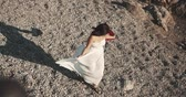 pegada : the Asian girl walks on a stony beach in a white dress