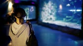 male animal : Young woman using tablet computer in oceanarium Stock Footage