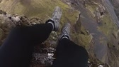 lookingdown : A hiker dangles his legs over the edge of a cliff Stock Footage