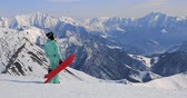udatnost : view of female snowboarder with snowboard in one hand and enjoying mountain Dostupné videozáznamy