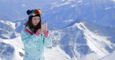 závodník : Female snowboarder using her smart phone, taking pictures of winter nature in the mountains