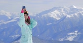 connettività : Female snowboarder using her smart phone, taking pictures of winter nature in the mountains