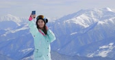 connettività : Female snowboarder using her smart phone, taking pictures in the mountains