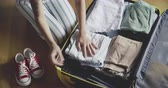Coseup of woman packing a luggage on wooden floor