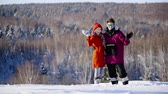 enjoying : Happy coulple waving hands to camera in mountain ski resort at sunny day. Winter, sport, holidays, relationship, love, xmas, lifestyle concept. Filmed on cinema camera, 10 bit color space.