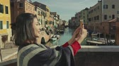 benátský : Stylish woman poncho top using mobile phone while in Venice Italy. Tourism, travel, lifestyle concept.