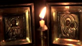 religious symbols : put out a candle in front of the icons of Jesus and the Mother of God