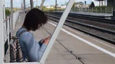 Woman commuter using mobile phone when waiting for the train on platform in small town Stock Footage