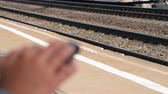 вид транспорта : Close-up shot of a woman browsing web on mobile when waiting for the train platform. Focus on the rail tracks Стоковые видеозаписи