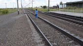 township : Young woman with backpack walking along the railway tracks in the countryside Stock Footage