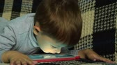 рабочий стол : Four year old boy choosing a game on digital tablet and waiting for it to upload. He is eager to have fun with playing on pad