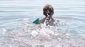 Little boy learning to swim with water wings and splashing water with feet. Active child on hot summer day