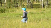Little boy running in high grass in the woods. Fun and active leisure in the countryside
