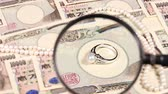 loupe : Japanese yen bill and magnifying glass and jewelry Stock Footage