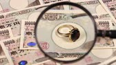 economy : Japanese yen bill and magnifying glass and jewelry Stock Footage
