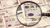 законопроект : Japanese yen bill and magnifying glass