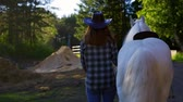 A girl in a cowboy hat walks with a horse on a farm. Стоковые видеозаписи