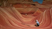 képződés : people taking pictures in the wave a of northern Arizona Stock mozgókép