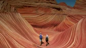 camadas : couple walks by camera and through the wave of northern Arizona Vídeos