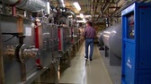 engenharia : man walks through complex machine room
