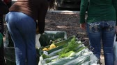 розничная торговля : people sort through fresh vegetables at Farmers market