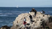 yat : rocky ocean shore with sightseers and sailboat Stok Video