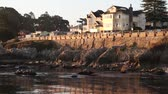 wealthy : houses above rocky shoreline at sunrise