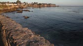 wealthy : calm ocean near houses on rocky shoreline Stock Footage