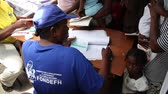 kayıtlar : recordkeeping at vaccination clinic in Haiti Stok Video