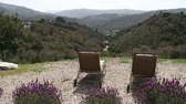 gramado : lavender, lounge chairs, and green valley below Stock Footage
