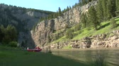 faaliyetler : Rocky canyon with river rafters preparing for trip Stok Video