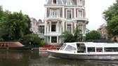 holandia : large home and wooden boat on Amsterdam canal