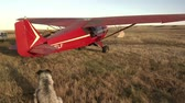 открыть : small red airplane takes off from field
