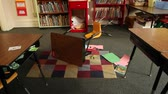 Shot of knocked-over desk and chair in classroom Wideo