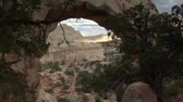 casado : couple sits under sandstone arch in Capitol reef national Park