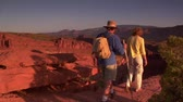 casado : couple stands on a red rock cliff and admires view Capitol reef national Park