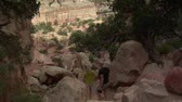 stel : paar wandelingen onder zandstenen boog in Capitol Reef National Park Stockvideo