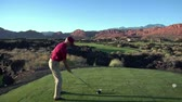 motorista : steadicam shot of man teeing off on golf course with sunset and red rock cliffs