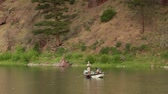 rybář : pullout shot of flyfishing drift boat on calm River with pine tree Dostupné videozáznamy