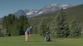 motorista : zoomed shot of man teeing off on golf course with snowy mountains indistance Vídeos