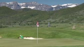 borovice : Man chips out of sand trap  to green with snowy mountains in distance