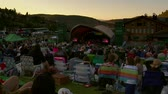 релаксация : crowd  in lawn chairs watches outdoor concert at sunset