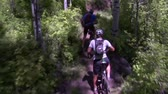 distante : Mountain bikers pedal down steep wooded trail