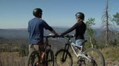 даты : Mountain biking couple pause for view Стоковые видеозаписи