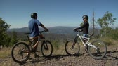 даты : Mountain biking couple stop to rest and see view